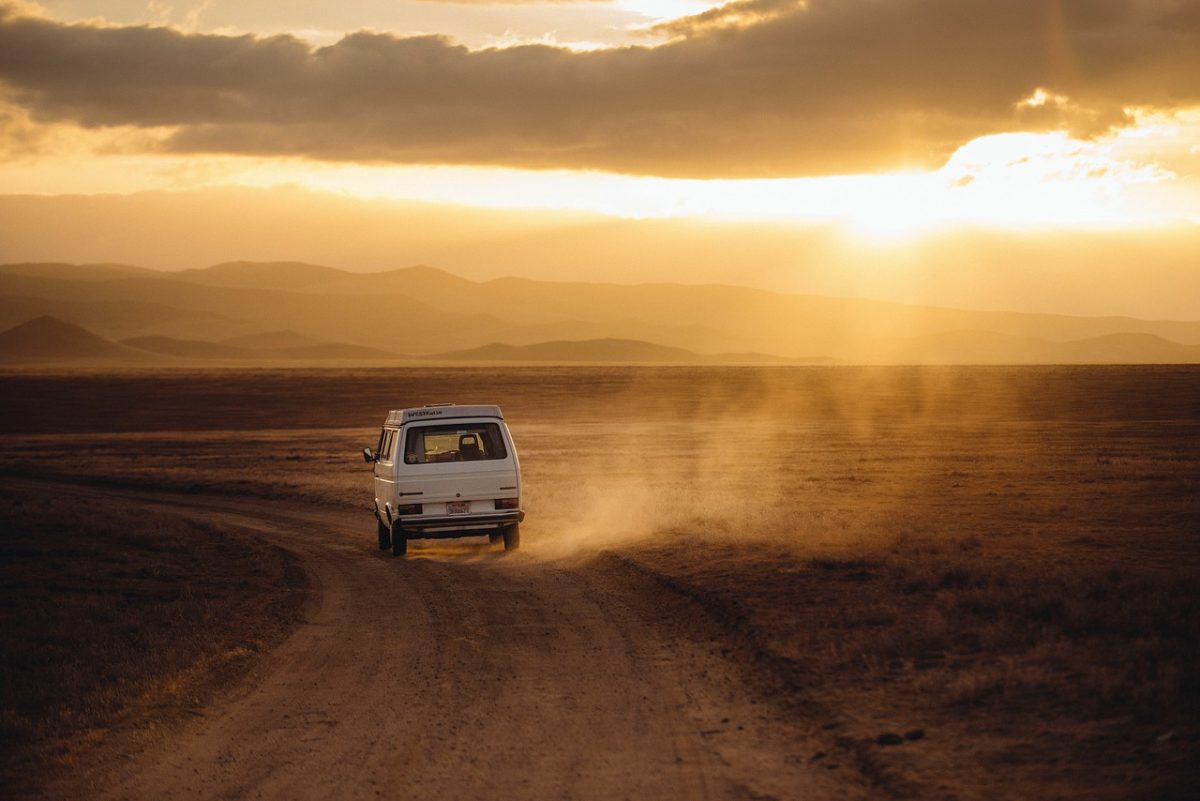 Volkswagen campervan traveling a dusty road