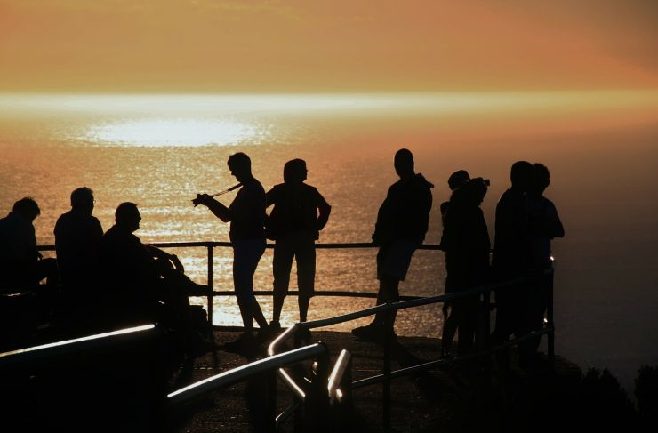 Group of travelers in silhouette at sunset