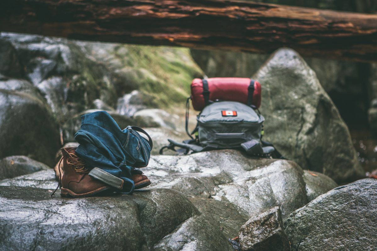 two gray and orange backpacks on gray rocks at daytime