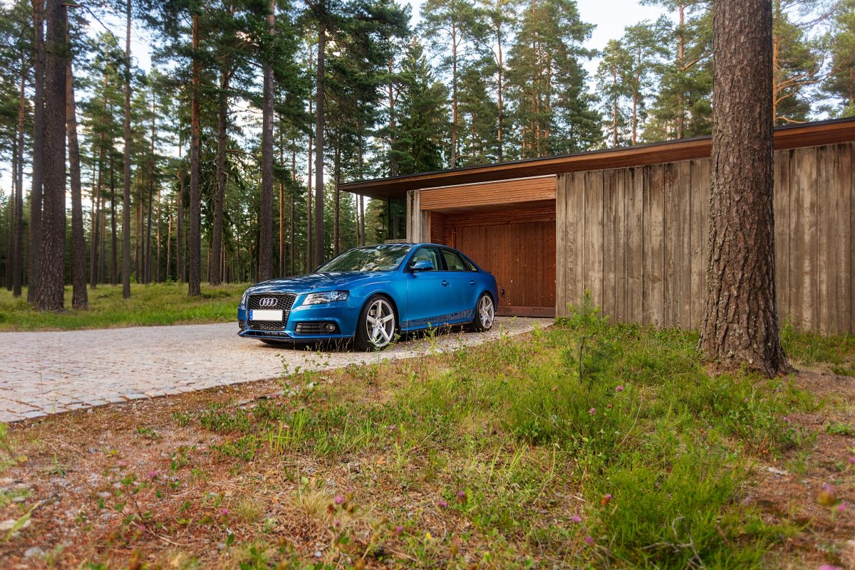 blue bmw m 3 parked near brown wooden house