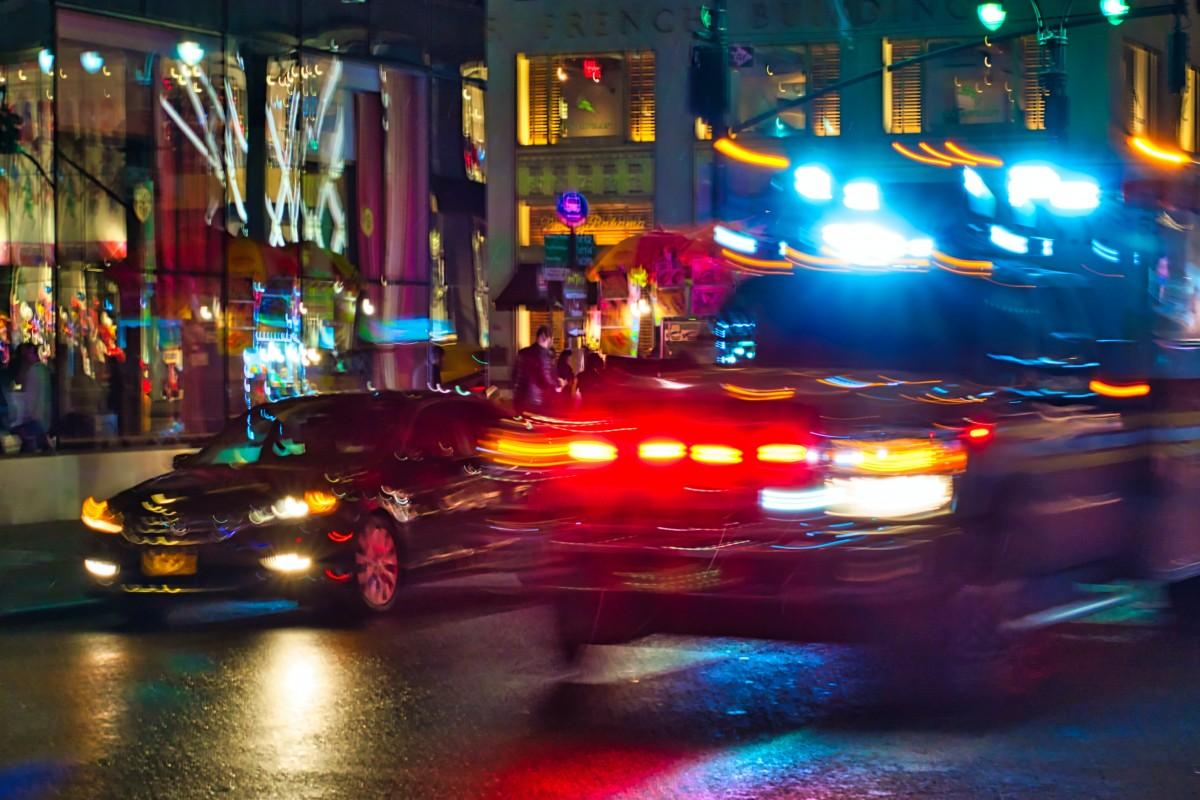An emergency vehicle moving through nighttime traffic on a New York Street.