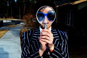 Style Tips Interpret the World person using magnifying glass enlarging the appearance of his nose and sunglasses