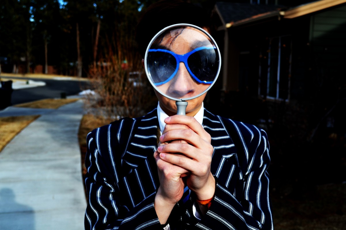 Side Gig Style Tips Interpret the World person using magnifying glass enlarging the appearance of his nose and sunglasses