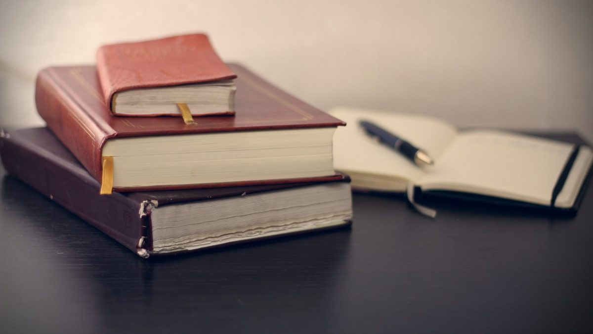 selective focus photography of three books beside opened notebook