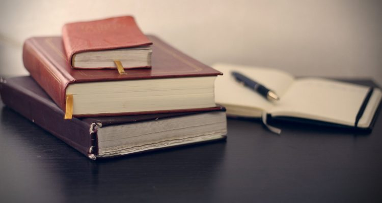 Concentration selective focus photography of three books beside opened notebook