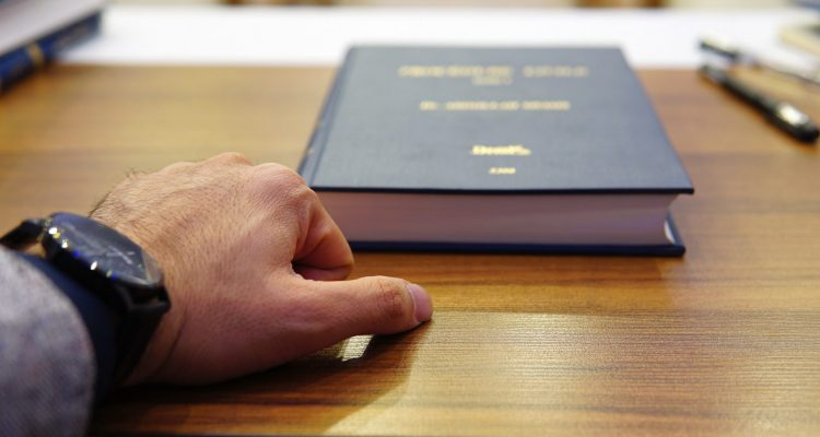 person holding black covered book on brown wooden table