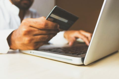 Shopping Online Credit Cards person using laptop computer holding card
