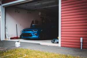 Car Insurance Car Enthusiast blue car parked beside red garage door