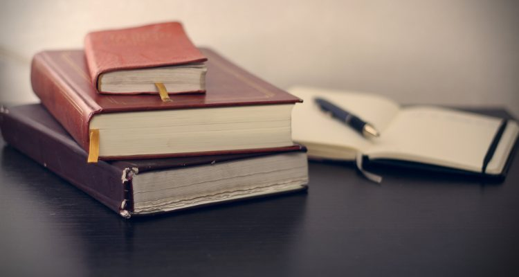 Trade Law selective focus photography of three books beside opened notebook