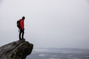 Outdoors activities person standing on gray rock