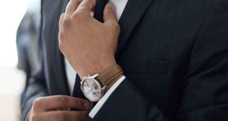 Dressing Well Dressing For The Workplace man wearing watch with black suit