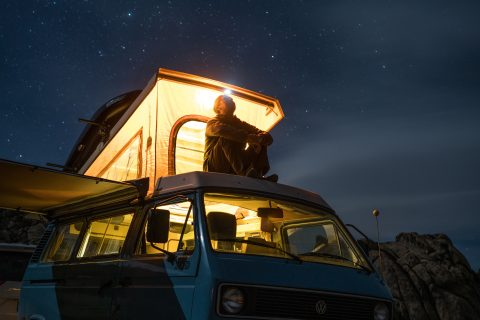 Off Road man sitting on top of blue van staring at sky during nighttime