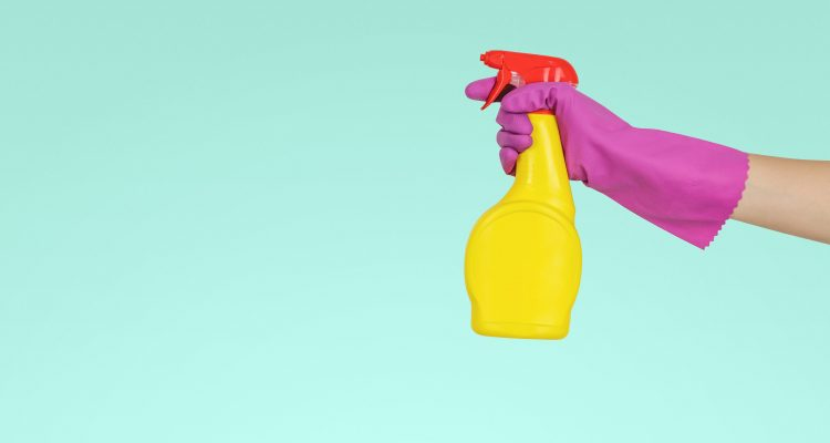Attention person holding yellow plastic spray bottle