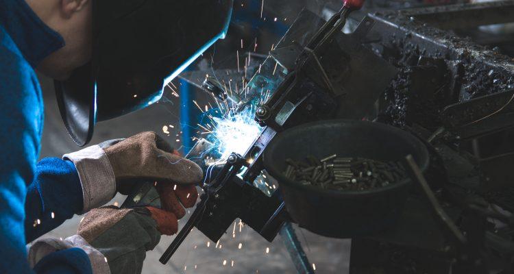MIG Welding man welding a black metal