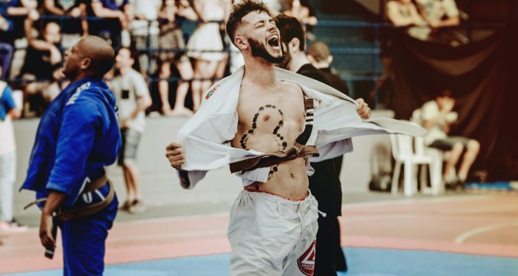 Achieve Anything Practicing Jiu-Jitsu man taking shit off surrounded with people