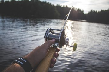Fishing Gear hobbies person holding black and silver fishing reel