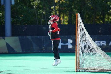 New Hobby Field Hockey person jumping wearing red and white head gear in front of net goal
