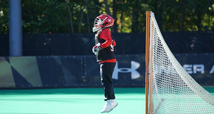 Field Hockey person jumping wearing red and white head gear in front of net goal