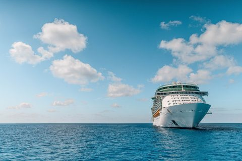 First-time Cruise white and blue ship on sea under blue sky and white clouds during daytime