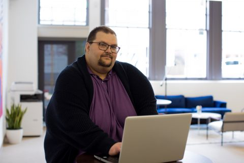 Gynecomastia close-up photography of man using laptop