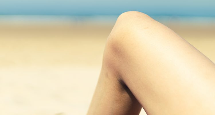 Knee Pain person sitting on white sand during daytime