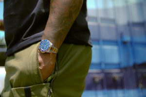 rolex green person wearing gold analog watch